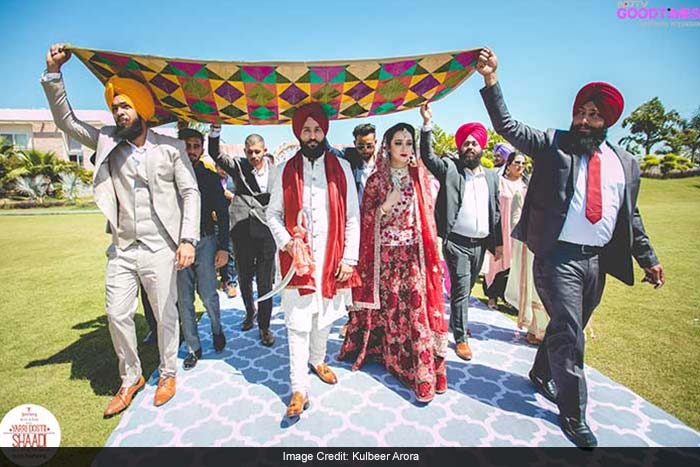 Amar and Simer are escorted by their families in traditional Sikh style, under a hand-woven Phulkari Dupatta.