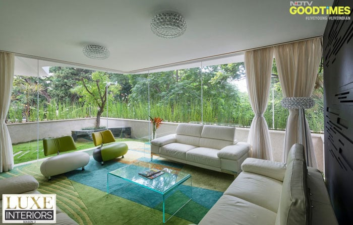Some muted furniture, glass walls overlooking nature, and a customized green carpet on the indoors. And that's how you bring the greens in.