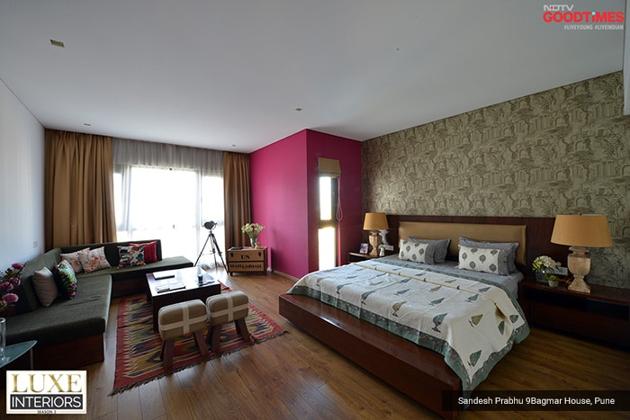 To amp up the master bedroom, Designer Sandesh Prabhu has adorned it with golden wallpaper. Spaces have been filled up with minimalistic furniture, and a pop of fuchsia pink in the accent wall breaks the monotony of the white ones.