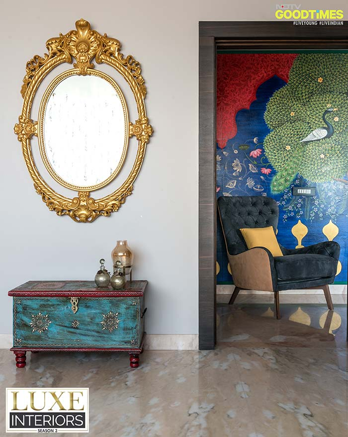 An ornate mirror, a traditional chest and a contemporary wing back chair clubbed with a striking wall art incorporating pichwai and bani thani art forms; now who wouldn't like to live in a setup like this?