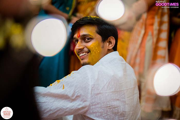 The groom Abhijeet manages to give our lens a smile as he continues to get covered in haldi.