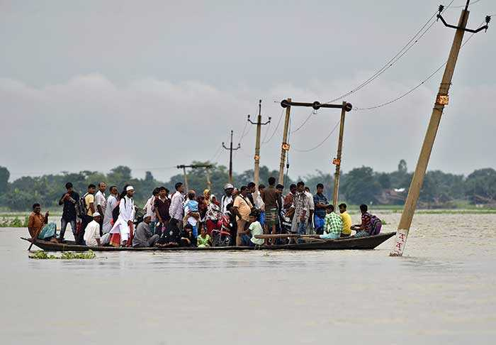 Villagers cross a flooded road on a boat in the Morigaon district of Assam (Reuters)