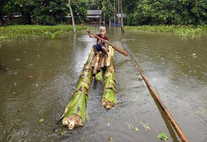 A child uses a makeshift raft in the flood-hit Kuthori village. (Reuters)