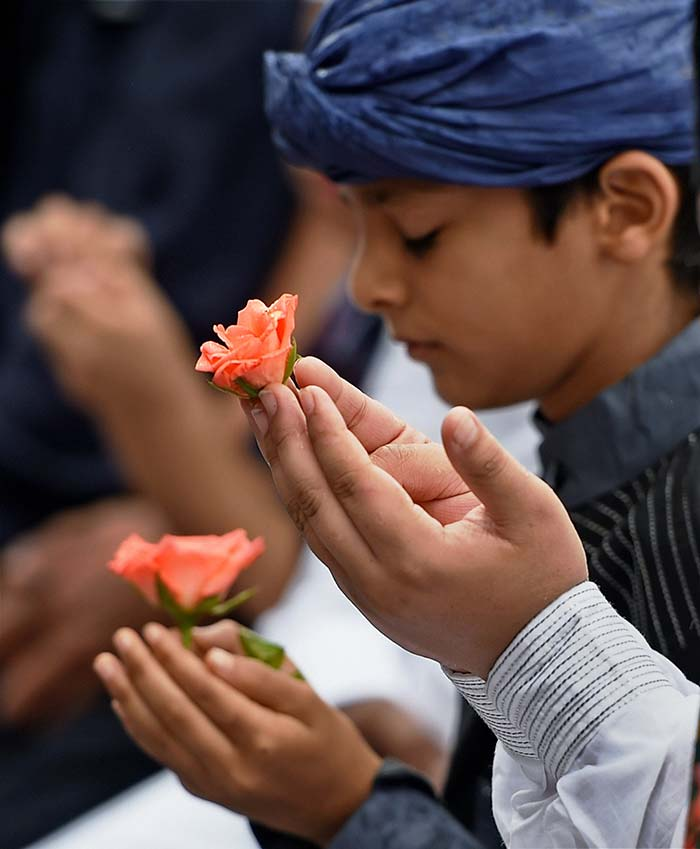 Children join Eid celebrations in Mumbai and offer prayers with flowers in their hands.