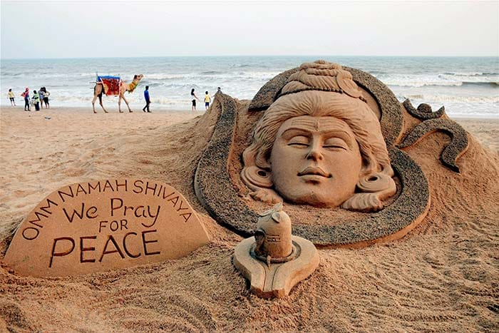 Sand artist Sudarshan Pattnaik creates a sand art on Lord Shiva on the eve of Maha Shivratri at Puri beach. (PTI Photo)