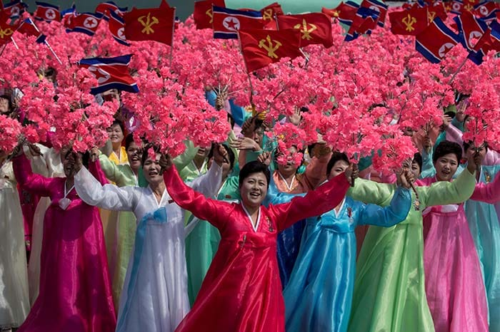 Women wearing traditional Korean dress wave flowers and shout slogans as they pass North Korea's leader Kim Jong-Un during a mass rally marking the 105th anniversary of the birth of late North Korean leader Kim Il-Sung in Pyongyang on April 15, 2017. (AFP)