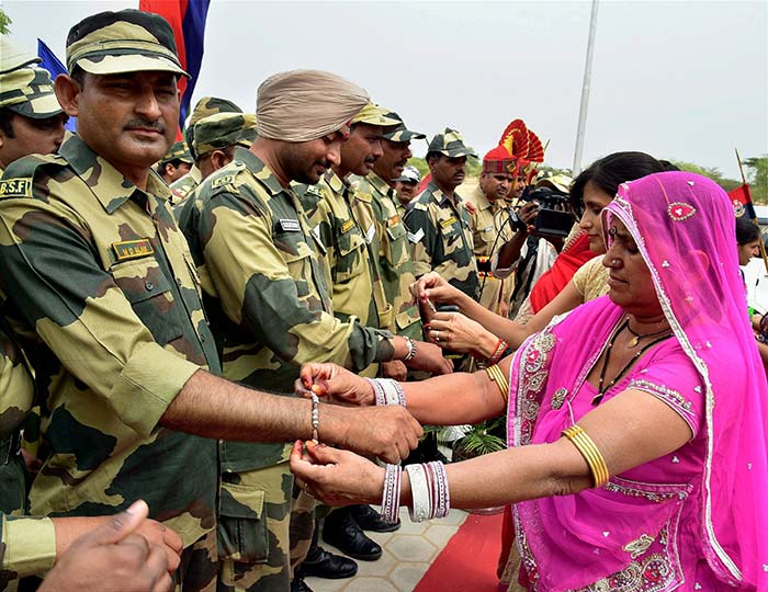 Women tying rakhis on the wrists of BSF personnel on Raksha Bandhan, in Bikaner on Monday. (PTI Photo)