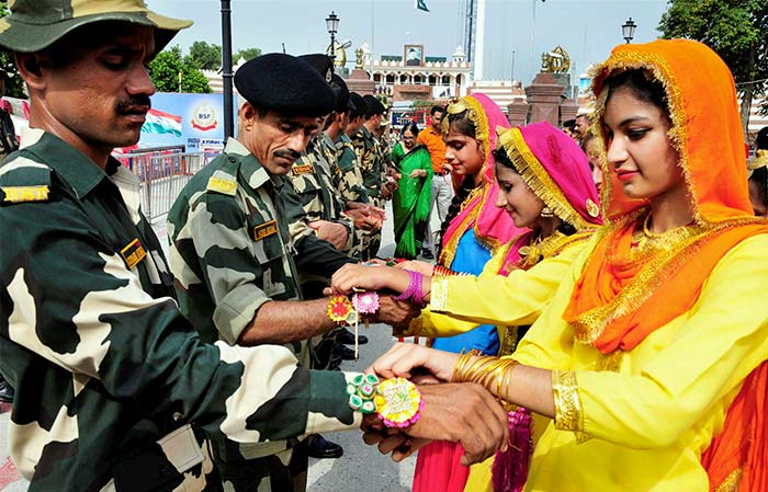Students in traditional attire tie rakhi on the wrists of Border Security Force (BSF) personnel during an event to celebrate Raksha Bandhan, at the India-Pakistan border joint check post at the International Border in Attari, on Monday. (PTI Photo)