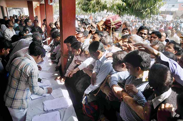 Election officers gather at a distribution centre to receive EVMs for their respective polling stations on the eve of polling in Allahabad.