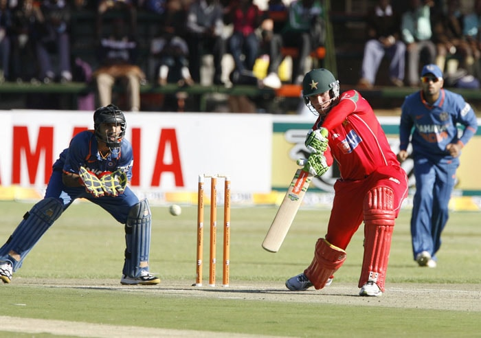 Zimbabwean batsman Brendan Taylor hits a shot in the watchful eyes of Indian wicket keeper Dinesh Karthik and Murali Vijay. Taylor top scored with 74. (AFP PHOTO)