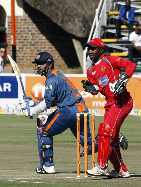 Indian batman Dinesh Karthik waits to see if he is safe to make a run as Zimbabwean wicketkeeper Tatenda Taibu awaits an opportunity for a run out at Harare Sports Club during the fourth ODI of the tri-series. (AFP Photo)