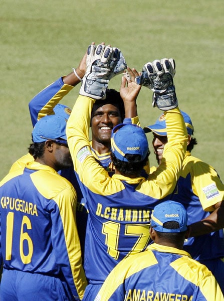 Sri Lankan bowler Thissara Perera and his teammates celebrate after he took the wicket of Indian batsman Dinesh Karthik in the fifth ODI of the Micromax Cup Triangular Series in Harare. (AFP Photo)