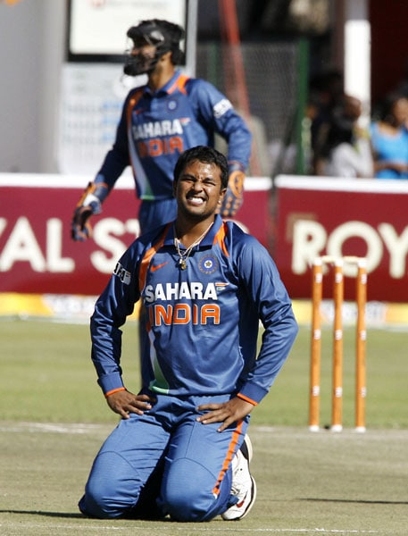 Indian bowler Pragyan Ojha is on the ground after missing the ball against Sri Lanka in the fifth ODI of the Micromax Cup Triangular Series in Harare. (AFP Photo)
