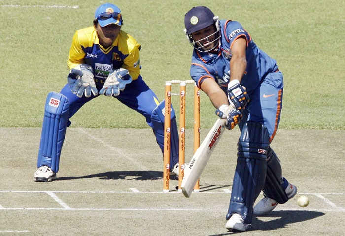 Indian batsman Rohit Sharma takes a shot as Sri Lanka wicketkeeper Dinesh Chandimal watches him in the fifth ODI of the Micromax Cup Triangular Series in Harare. (AFP Photo)