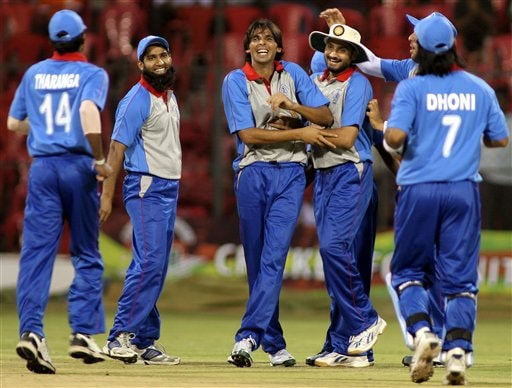 Asia XI's Mohammad Asif, center, is congratulated by teammates Mohammad Yousuf, second left facing camera, Harbhajan Singh, second right facing camera, and others after he dismissed Africa XI's AB De Villiers, unseen, during the first One-Day International Afro-Asian cricket match in Bangalore, India on Wednesday.