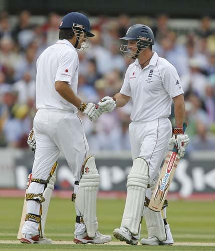 Alastair Cook is congratulated by Andrew Strauss after hitting a shot for 4 runs during the first day of the second Ashes Test at Lord's. (AFP Photo)