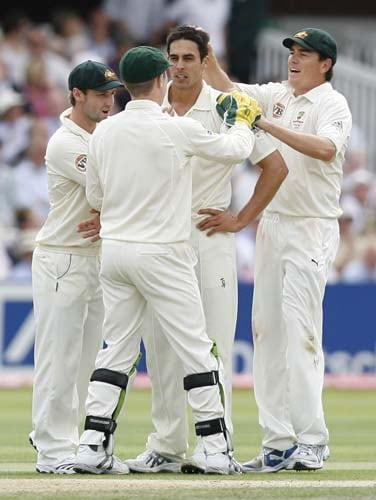 Mitchell Johnson is congratulated on taking the wicket of Alastair Cook by team mates during the first day of the second Ashes Test at Lord's. (AFP Photo)