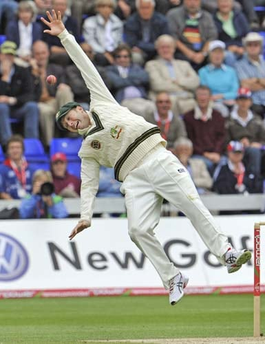 Michael Clarke leaps as he attempts to catch a ball as England bat in the first innings during the second day of the first Ashes Test in Cardiff. (AFP Photo)