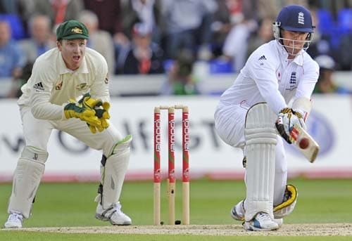 Graeme Swann reverse sweeps as Brad Haddin looks on during the second day of the first Ashes Test in Cardiff. (AFP Photo)