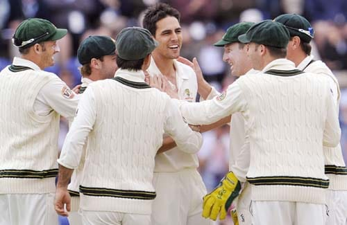 Mitchell Johnson is congratulated by teammates after dismissing Stuart Broad during the second day of the first Ashes Test in Cardiff. (AFP Photo)