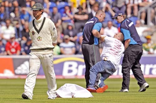 Pitch stewards remove a man carrying a banner as Ricky Ponting looks away on the final day of the first Ashes Test in Cardiff. (AFP Photo)