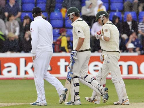 Marcus North and Michael Clarke chat to Graeme Swann as they leave the field for a rain delay on the third day of the first Ashes Test between England and Australia in Cardiff. (AFP Photo)