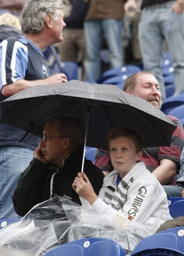 Cricket fans are seen during a rain break on the third day of the first Ashes Test between England and Australia in Cardiff. (AP Photo)