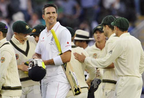 Kevin Pietersen looks towards the incoming rain as the Australian team congratulate each other on the fourth day of the first Ashes Test in Cardiff. (AFP Photo)