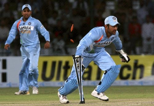 India captain MS Dhoni runs out Salman Butt to give India their first wicket.