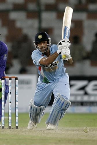 India captain M.S. Dhoni drives one away during his half century against Sri Lanka.