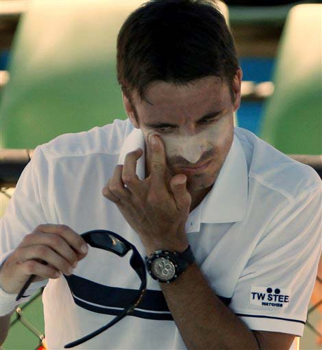 Spain's Tommy Robredo puts sun cream on his face as he plays Bobby Reynolds of the US during their men's singles match at the Australian Open in Melbourne on Monday. (AP Photo)