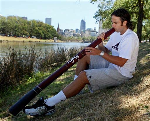 Chile's Fernando Gonzalez plays a didgeridoo as he sits on the banks of the Yarra river in Melbourne on Monday. (AP Photo)