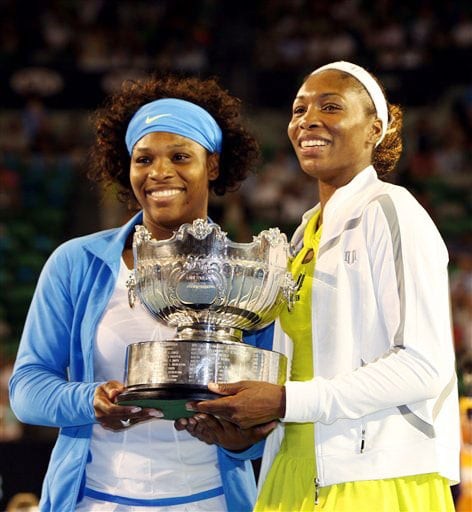 Serena Williams of the United States and her sister Venus smile as they hold the trophy after beating Japan's Ai Sugiyama and Daniela Hantuchova of Slovakia in the Women's doubles final at the Australian Open in Melbourne.