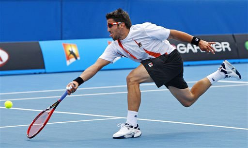 Janko Tipsarevic of Serbia stretches to volley to Croatia's Marin Cilic during a Men's singles match at the Australian Open in Melbourne.