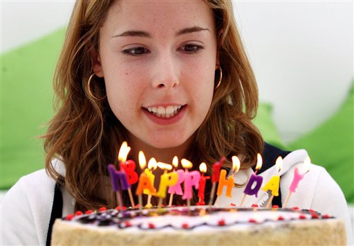 France's Alize Cornet holds a birthday cake presented to her mark her 19th birthday at the Australian Open in Melbourne on Thursday. (AP Photo)