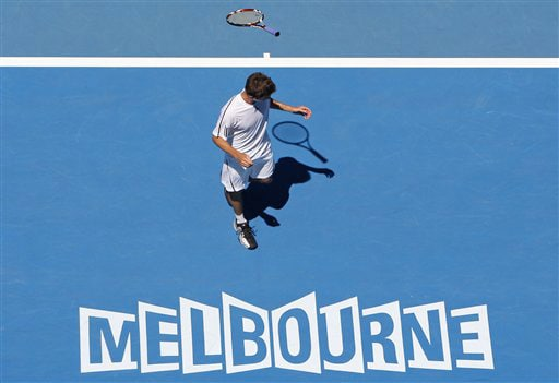 France's Gilles Simon throws his racquet over his head as he plays France's Gael Monfils during their men's singles match at the Australian Open in Melbourne on Monday. (AP Photo)