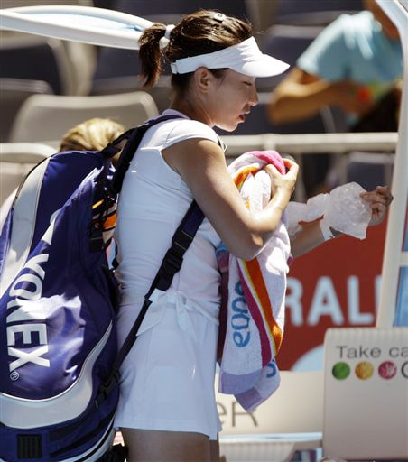 China's Zheng Jie walks off the court as she retired injured in her women's singles match against Russia's Svetlana Kuznetsova at the Australia Open in Melbourne on Monday. (AP Photo)