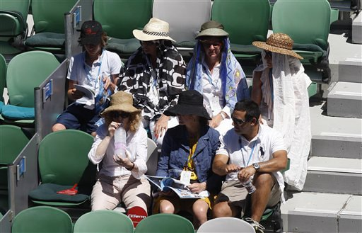 Spectators protect themselves from the sun as they watch Russia's Elena Dementieva play Spain's Carla Suarez Navarroin a women's singles match at the Australian Open in Melbourne on Wednesday. (AP Photo)