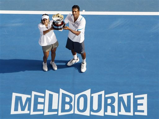 Sania Mirza and Mahesh Bhupathi hold the trophy during the awarding ceremony after beating Nathalie Dechy and Andy Ram during the mixed doubles final match at the Australian Open in Melbourne.
