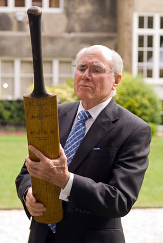 Former Prime Minister of Australia John Howard AC, poses with one of two 'Bradman Cricket Bats' at the Goring Hotel in central London on Monday. (AFP Photo)