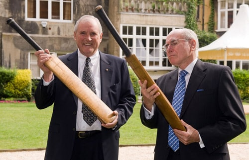 Michael Ball and John Howard AC, pose with two 'Bradman Cricket Bats' at the Goring Hotel in central London on Monday. (AFP Photo)