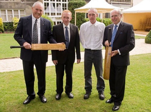 Michael Ball, Eugene Withers, Martin Withers and John Howard AC pose with two 'Bradman Cricket Bats' at the Goring Hotel in central London on Monday. (AFP Photo)