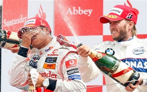 BMW Sauber driver Nick Heidfeld of Germany sprays champagne to celebrate his second position as McLaren Mercedes driver Lewis Hamilton of Britain who won the race wipes his face on the podium after the British F1 World Championship race in Silverstone, England on July 6, 2008.