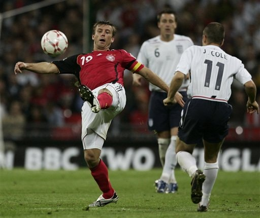Germany's captain Bernd Schneider, left, controls the ball in front of England's Joe Cole, right, during a friendly soccer match between England and Germany at the Wembley Stadium, in London, Wednesday Aug. 22, 2007.