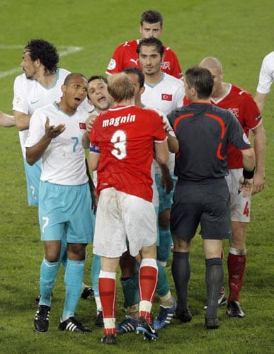 Turkey's Mehmet Aurelio, foreground left, argues with Switzerland's Ludovic Magnin, foreground center, as referee Lubos Michel, right, looks on, during the group A match between Switzerland and Turkey in Basel, Switzerland.