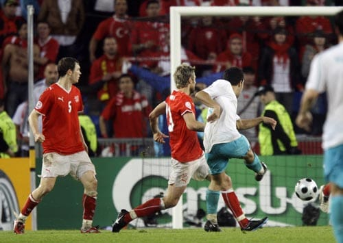 Turkey's Arda Turan, right, scores the winning goal past Switzerland's Valon Behrami, second left, during the group A match between Switzerland and Turkey in Basel, Switzerland.