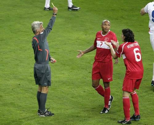 Referee Peter Frojdfeldt from Sweden, left, awards the yellow card to Turkey's Mehmet Aurelio, center, as Turkey's Mehmet Topal protests during the group A match between Turkey and Czech Republic in Geneva, Switzerland.