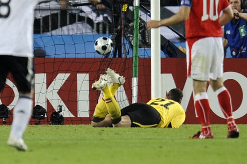 Austria's Juergen Macho looks at the ball bouncing into the net after Germany's Michael Ballack, unseen, scored the opening goal after shooting a free kick during the group B match between Austria and Germany in Vienna.