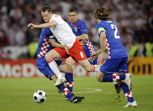 Poland's Jacek Krzynowek, center, tries to makes his way through the Croatian defense during the group B match between Poland and Croatia in Klagenfurt, Austria.