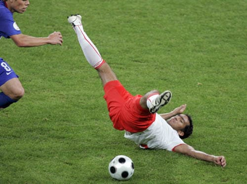 Poland's Roger Guerreiro, right, falls during the group B match between Poland and Croatia in Klagenfurt, Austria.